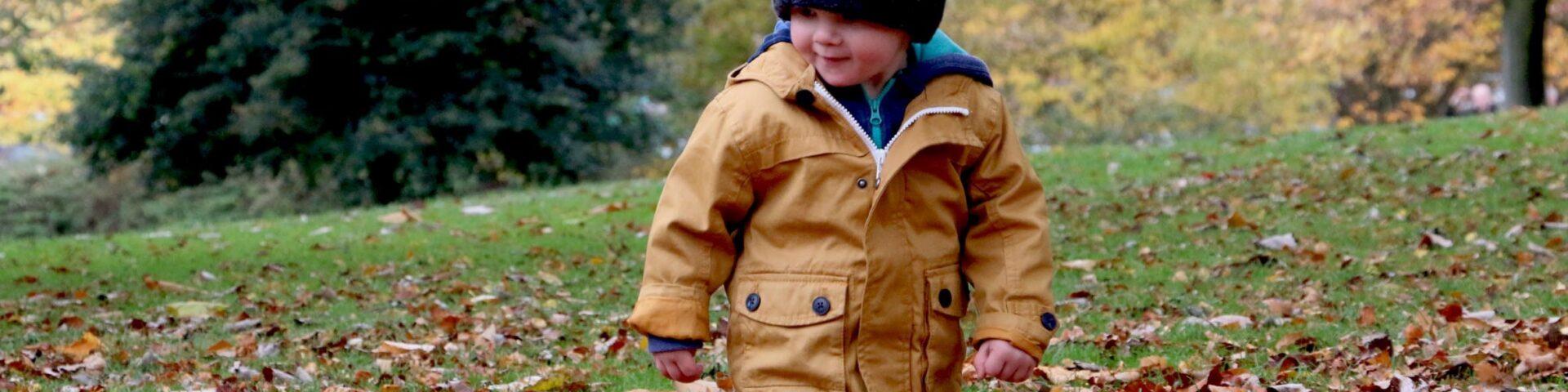 child in bobble hat walking in autumn leaves