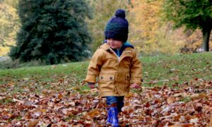 child in bobble hat walking in autumn leaves