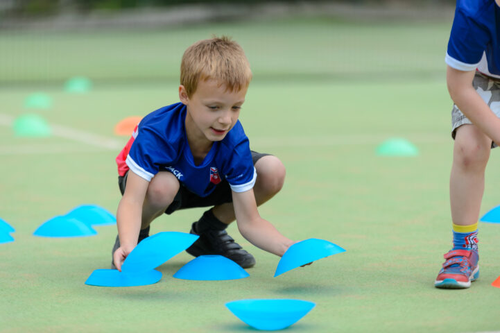 Child placing cones on ground