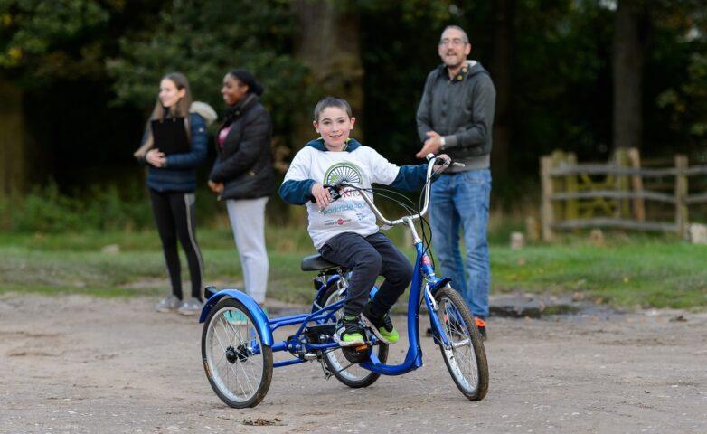 Boy using adaptive bicycle