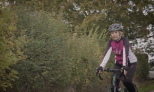 Woman with hearing loss cycling down country lane