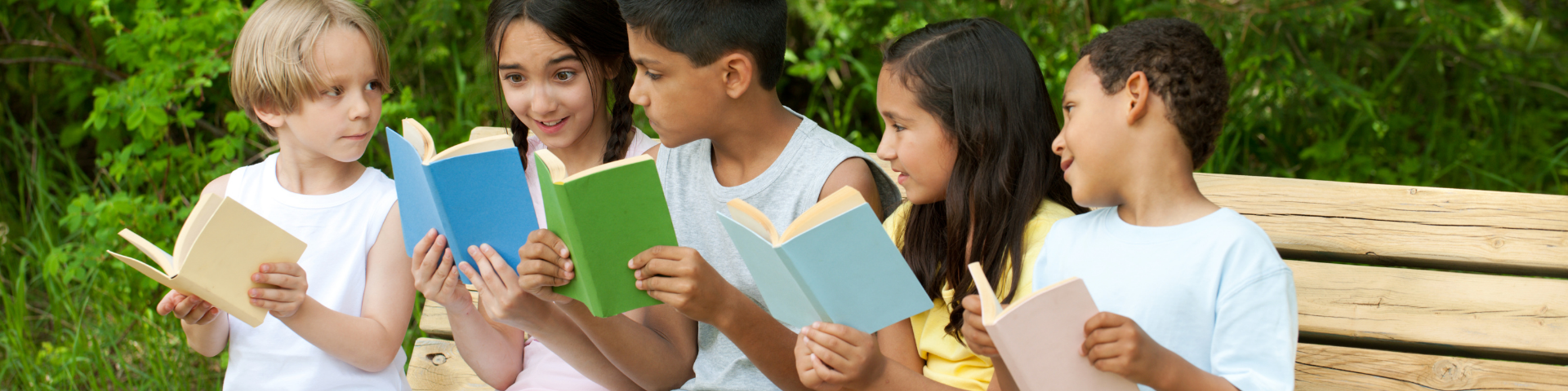five children reading books on a park bench