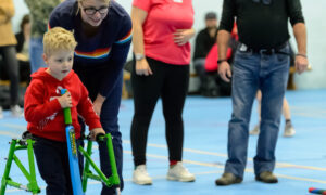 Little boy with a walking frame playing accessible cricket in a sports hall